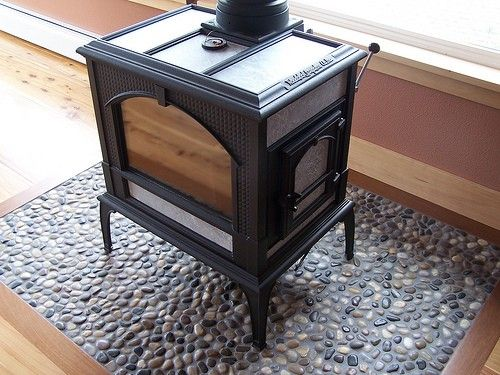 Here is the little woodstove, sitting on the pebbled surface, perfect for the beach cabin