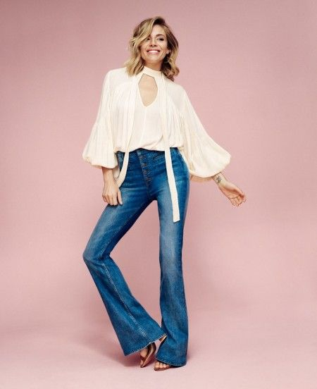 Posing in a studio, Sienna Miller wears a white blouse with puffy sleeves and flared denim from Lindex's spring 2016 collection