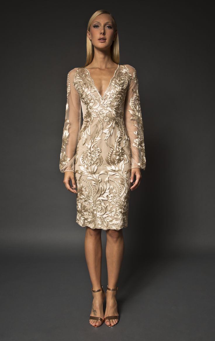 Gold lace embellished knee length dress with long sleeves. The Elias dress is a stunning gold floral lace embellished dress. It is designed as a slim fit dress and features a deep v neckline, long sheer sleevesand an above the knee sophisticated look. #cocktail #gold #lace #embellished #sleeves #specialoccasion