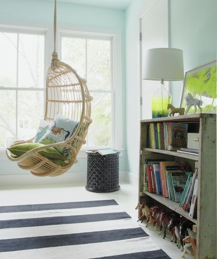 Pale blue walls complement the green view. Warm textures, like wicker, velvet, and distressed wood, help a sparsely furnished space feel soft and friendly.