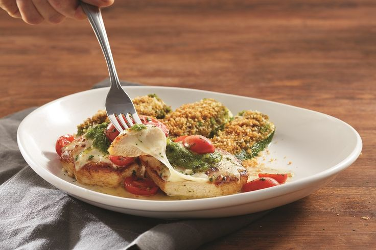 Olive Garden's Chicken Marghertiais acombination of grilled chicken breasts topped with fresh tomatoes, mozzarella, basil pesto and a lemon garlic sauce, served with Parmesan crusted zucchini.