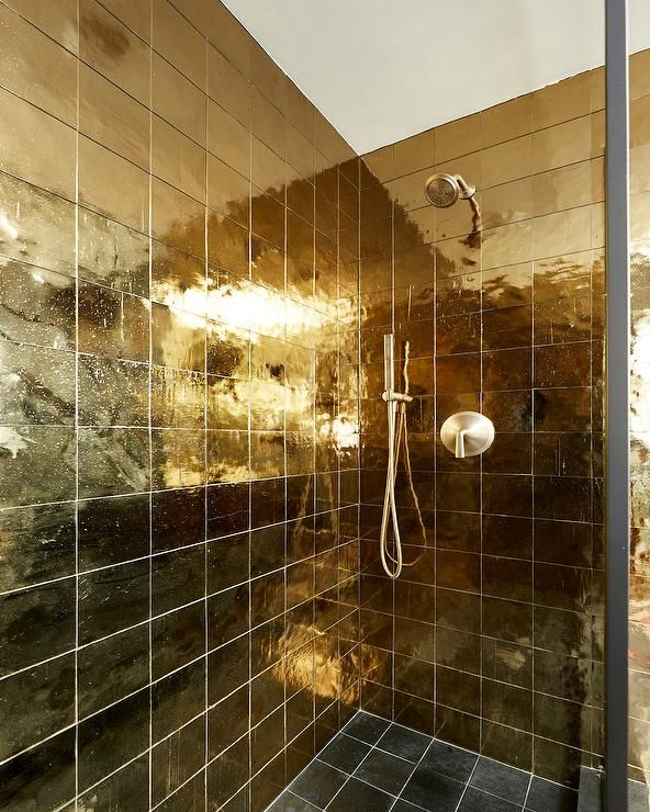 A Brushed Gold Shower Head Is Mounted To Shiny Gold Grid Shower Wall Tiles Over Black Grid Floor Tiles Gold Tiles Bathroom Shower Wall Gold Shower