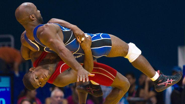 Teyon Ware, dos Estados Unidos, é arremessado pelo cubano Livan Lopez em combate da luta olímpica