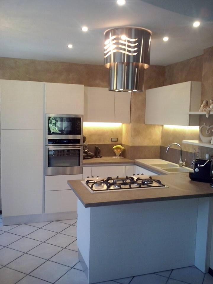 Cucina realizzata abbinando il modello Easy polimerico con finitura larice spazzolato ad un piano di lavoro color granito marrone con kappa lampadario Faber Vertigo