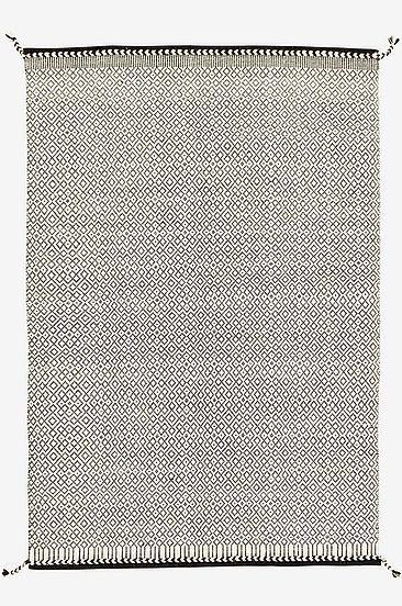 Mjuk ullmatta vävd i dekorativt mönster. De flätade detaljerna i kombination med den grafiska färgsättningen gör att mattan blir modern och trendig Material: 80% ull, 20% bomull. Storlek: 140x200 cm. Beskrivning: Handvävd matta av garnfärgad ull, med varp av bomull och dekorativa tofsar i hörnen. 1900 g/m2. Skötselråd: Kemtvätt. Tips/råd: Matcha med NORBELLO om du vill inreda med fler mattor i samma stil.