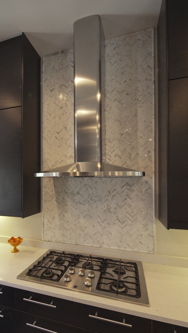 Limestone tiles layered in a herringbone pattern create a focal point behind  the range hood. - 14 Best Images About Backsplashes Behind Range On Pinterest