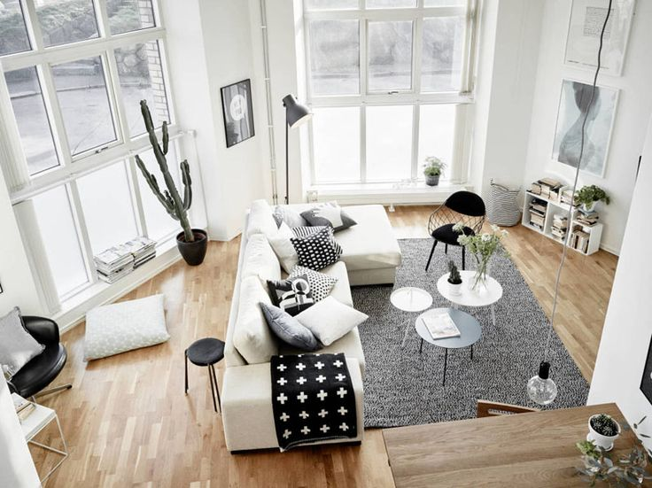Get some interior design ideas by looking at 15 living room layouts from above // Big windows, simple furniture, and lots of pillows make this living room a bright space that's great for relaxing in. A gray rug helps to anchor the sofa in the oddly shaped room.