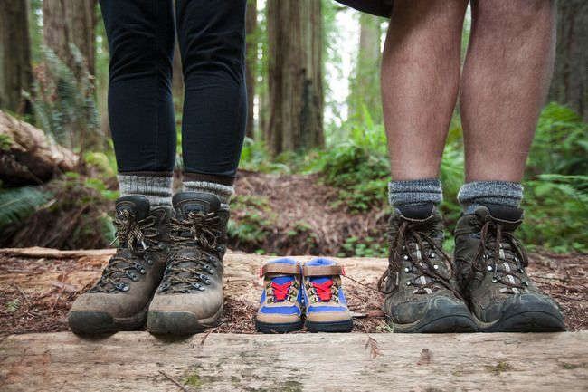Expecting parents use a pair of small hiking boots in line with their own to announce the arrival of their new baby