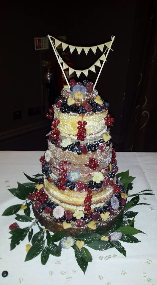 Naked Wedding Cake  using a combination of raspberry and lemon sponge, raspberries, redcurrants , blackberries and blueberries. Crystalized edible flowers from Meadowsweet Flowers