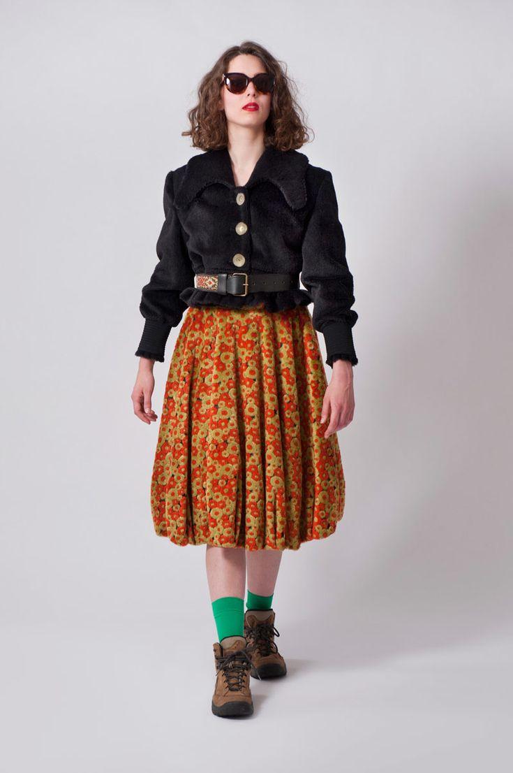 Groen/oranje rok van teddybont met een ondergrond van fijne zwarte tule. Blauw kort jasje van namaakbont en aangesnoerde mouwen van breed blauw elastiek.