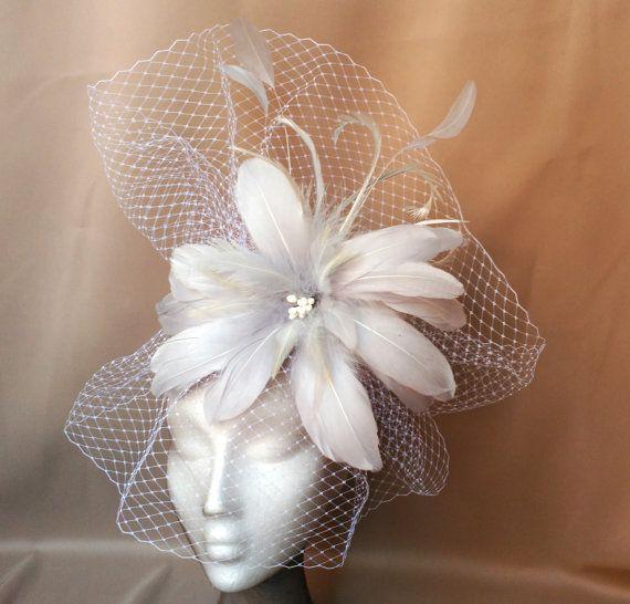 Hermoso tocado de flor gris y velo blanco. El tocado ha sido decorado con una gran flor gris de plumas, hecha a mano, coronada con plumas blancas y