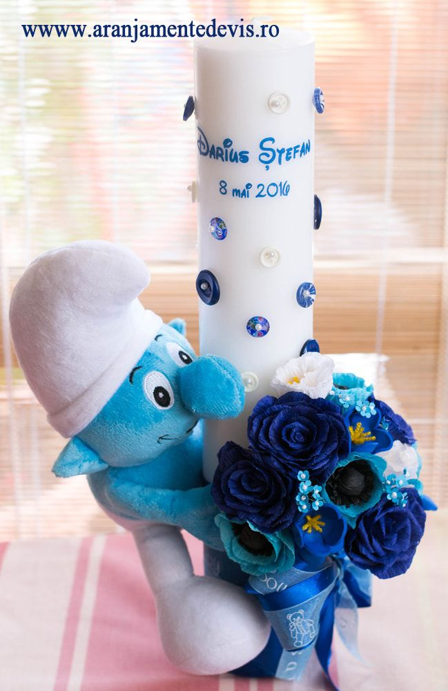 Lumanare de botez pentru botez cu tematica strumf si decorata cu flori realizate handmade.Modelul poate fi realizat si cu alte jucarii de plus sau alte culori ale florilor.