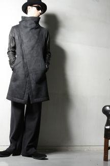 ウールのコート地をワックスコーティングで風合いのある表情に仕上げたスタンド衿のコートです。身頃はIラインながらも腰の位置を高く見せる独特のパターンで美しいシルエットを実現。袖にはLAMBレザーを使用しており、互いに存在感のある異素材の掛け合わせがbajraらしい1着です。