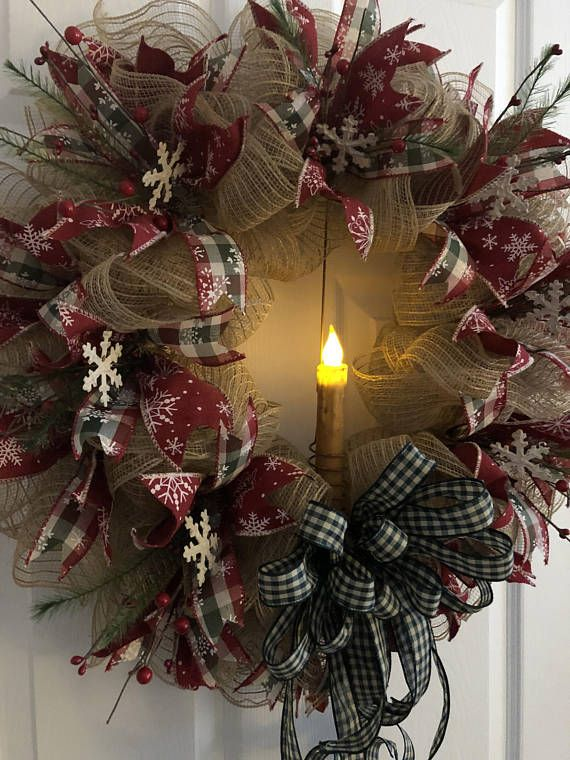This primitive Christmas Wreath is adorned with rustic rusty metal snowflakes and red pip berries, berries and greenery. A large flickering candle accents the center. The wreath is made of ivory poly burlap mesh and accented with reddish burgundy snowflake ribbon and checked ribbon als