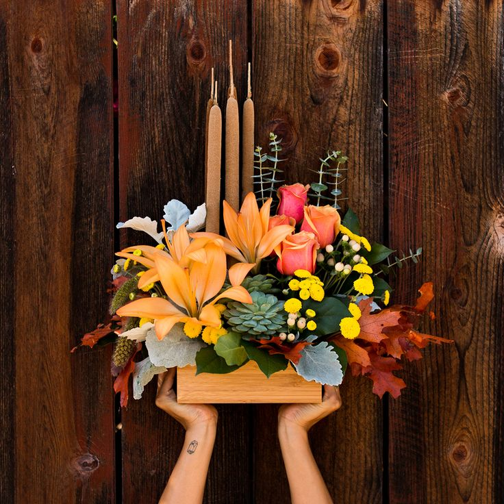 Modern fall flower bouquet with succulents, orange lilies, bright roses, yellow chrysanthemums and cattails in a rectangular bamboo container. #fall #bamboo #flowers