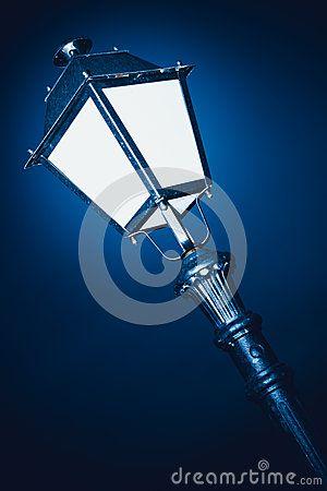 Lamp post lit at night.