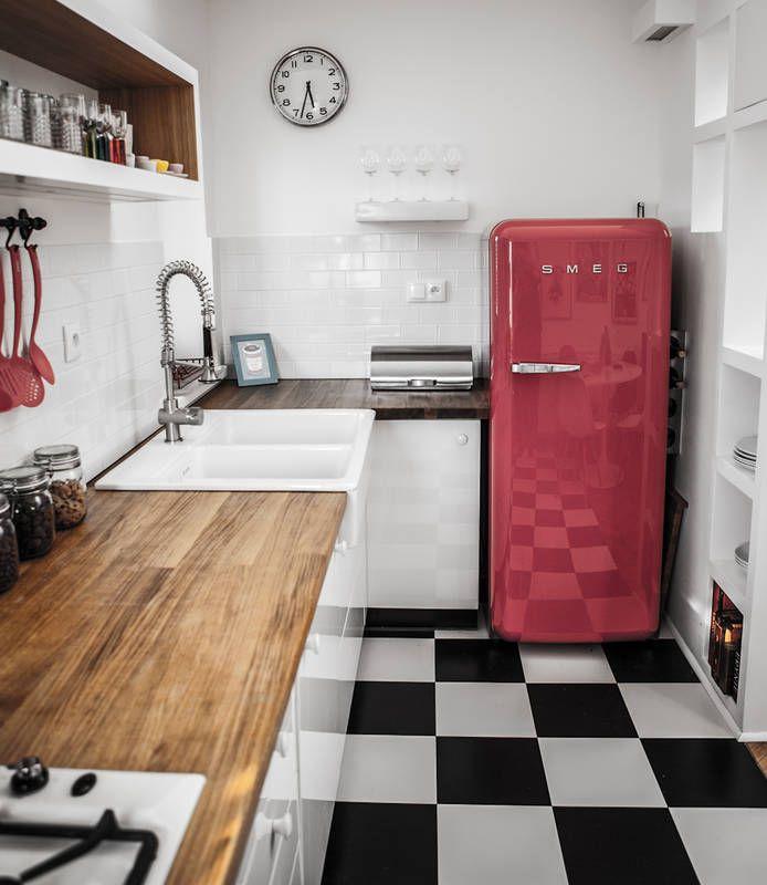 Czarno-biała szachownica na posadzce, gładkie białe meble i kafle na ścianie potrzebowały towarzystwa mocnego akcentu. Jest nim czerwona lodówka marki Smeg, stylizowana na modele retro. Wystrój kuchni uszlachetniają i ocieplają solidne drewniane blaty.