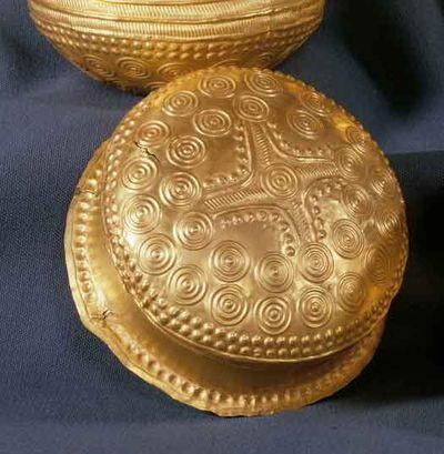 """Hvordan er guldskålene fremstillet?  Bronzealderens guldskåle er sandsynligvis fremstillet ved en gammelkendt drivnings-teknologi, der hedder """"knopning"""". Her hamrer man på den ene side af en cirkulær, forholdsvis tyk, guldplade. Man bruger en drivningshammer med rundet slagflade mod et hårdt underlag. Der startes midtfra og ud i en tæt spiral rundt om pladen. Ved hamringen strækker guldpladen sig opad, og til sidst bliver genstanden skålformet. Når pladen er hamret tynd, skal den opvarmes…"""