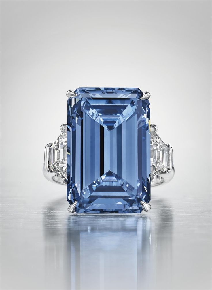 THE OPPENHEIMER BLUE -  A SENSATIONAL COLOURED DIAMOND RING -  Set with a fancy vivid blue rectangular-cut diamond, weighing approximately 14.62 carats, flanked on either side by a trapeze-shaped diamond, mounted in platinum. The diamond was previously owned by Sir Philip Oppenheimer, a member of the family that once controlled the De Beers Mining Company. Auction Price Realized $58,002,681 USD