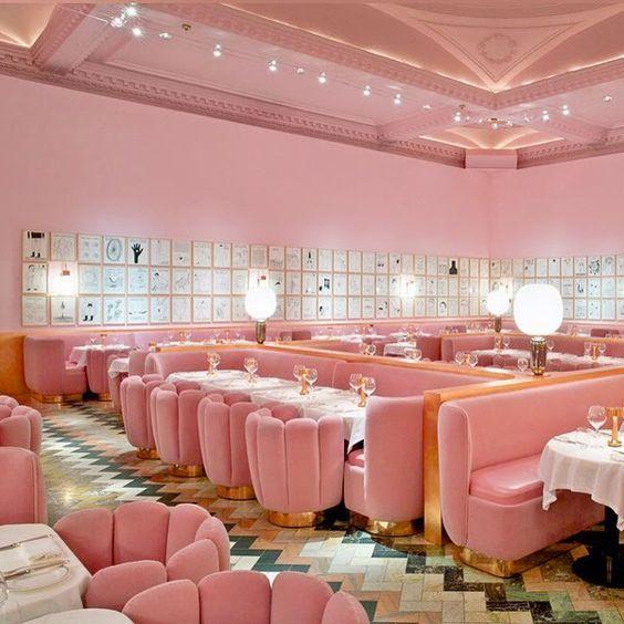 Une salle de restaurant rose bonbon avec des détail en laiton