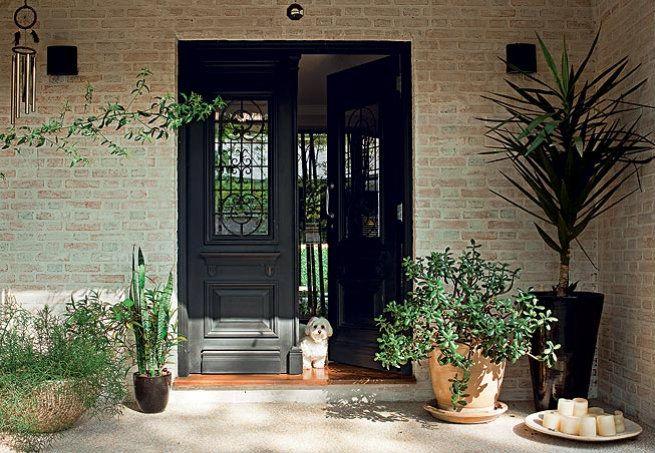 Os vasos grandes compõem a entrada de estilo inglês, com porta antiga de duas folhas de madeira entalhada, compradas em uma loja de demolição