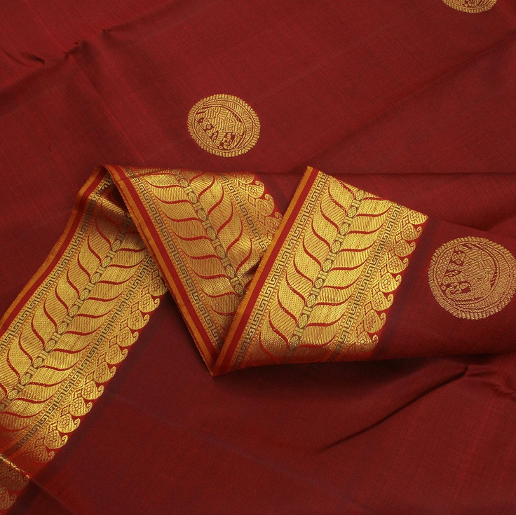 Woven in maroon, this Sarangi sari's body features golden medallions bearing diamonds and elephants inside them. The pallu meanwhile is simply spectacular in its lavish fine zari, woven into dazzling figures of yalis, zigzags, wheat stalks, and prayer beads—the entire mustard fabric illuminated by golden zari. Finally, golden festoons of mangoes, wheat stalks, and prayer beads adorn the red borders. The result is a stunning classic for a phenomenal woman. Code 390118991