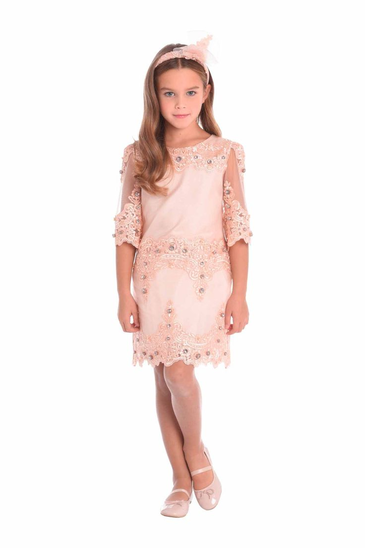 Luxury dress in beautiful peach pink tulle embroidered with an ornate floral design. The A-line dress has 3/4 length scalloped sleeves, round neckline and scalloped hem. The whole dress is embellished with sparkling pink stones hand sewn one by one.DELIVERY 7/14 DAYS