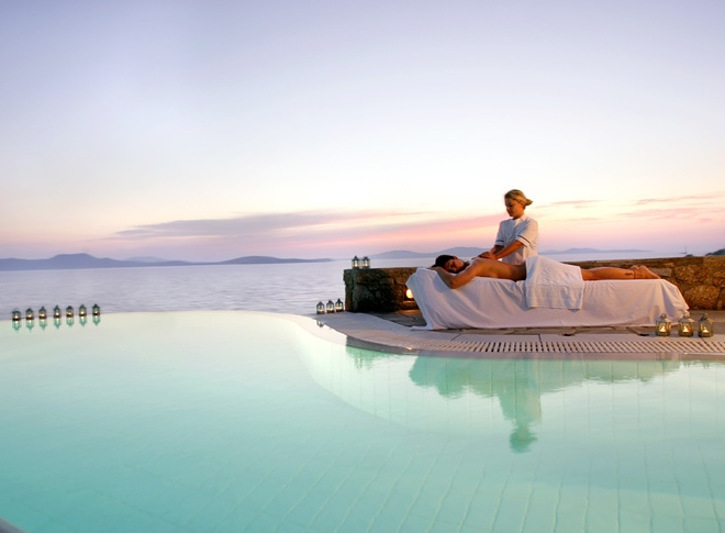 The ultimate relaxation massage experience by the Mykonos Grand 5 Star Luxury Resort & Hotel pool, with a view of the Aegean sea.
