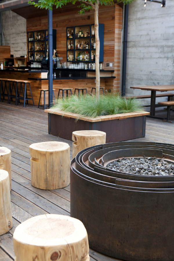 Spiral fire pit, notched wood seats, planter, and exterior bar space