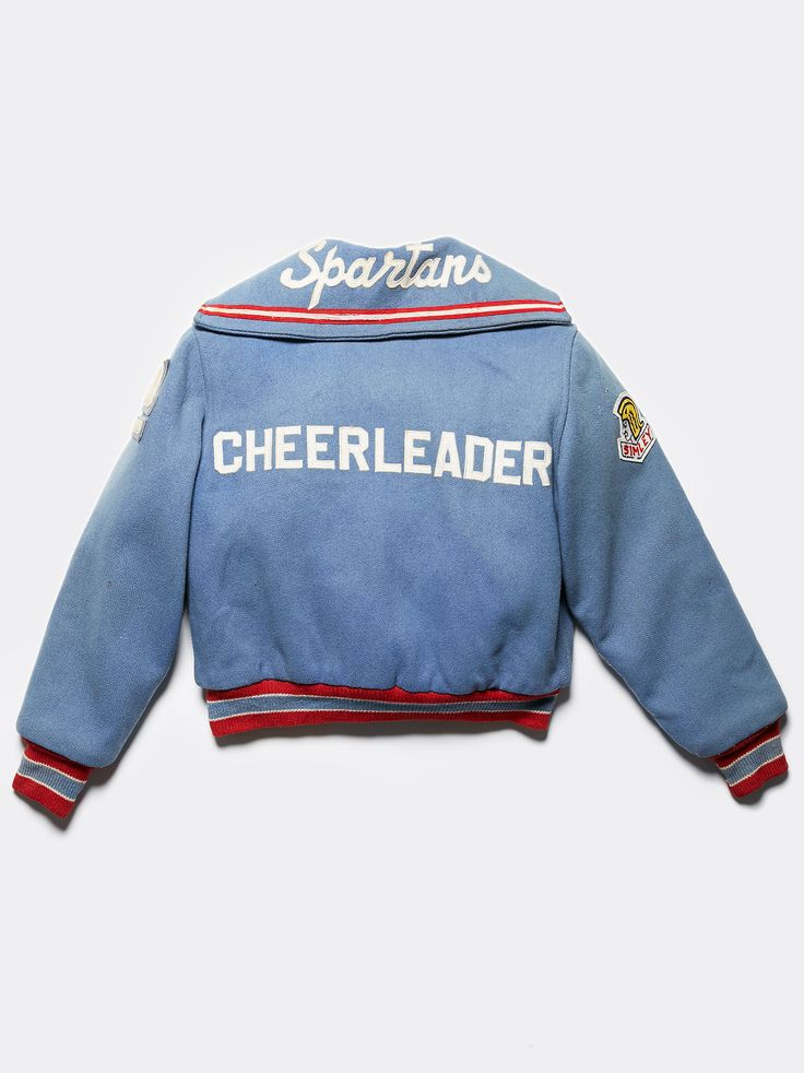 Vintage 1960s Cheer Letterman Jacket | Vintage from the 1960s this white and blue wool cheerleader letterman jacket featuring patched and embroidered with Nancy. Two front pockets and snap button closures.