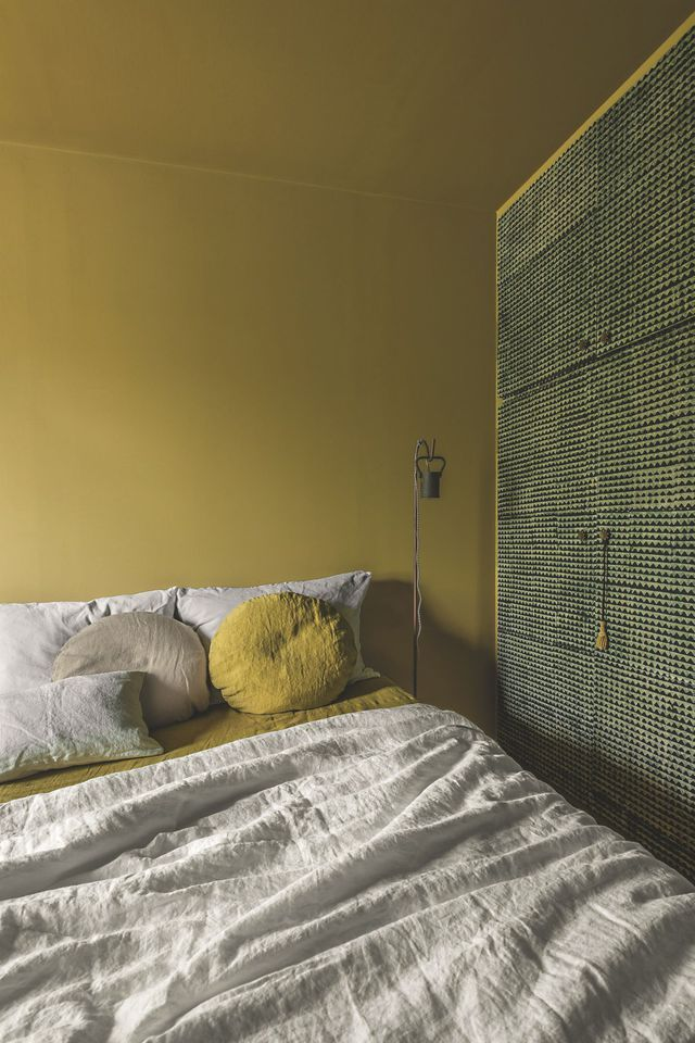 Dans ce lit en coton et lin lavé, les coussins se fondent dans le bronze doré de la peinture