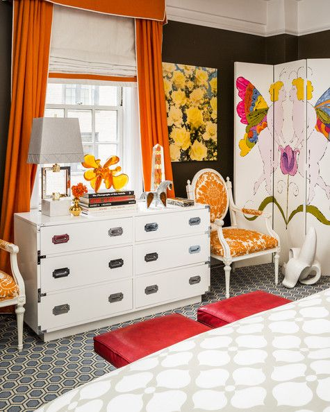 Black Bedroom - A pair of upholstered armchairs flanks a white bureau amid colorful curtains and accessories