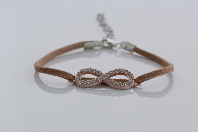 Rose-gold colour diamante infinity charm on a tan suede-look bracelet by Haute and Tidy on hellopretty.co.za