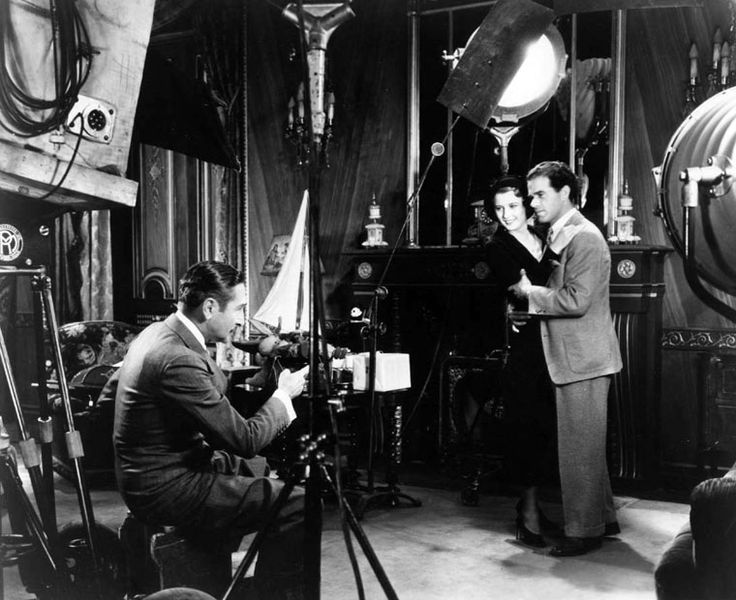 Director Frank Capra demonstrates to Adolphe Menjou how to handle Barbara Stanwyck in a scene from