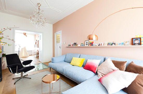 Sala de estar ampla com paleta de cores em tons claros de rosa e azul, com mix de almofadas em amarelo e marron. Os acessórios na estante da parede dão mais energia ao local. Para um ambiente mais claro, substitua a cadeira preta por uma branca.