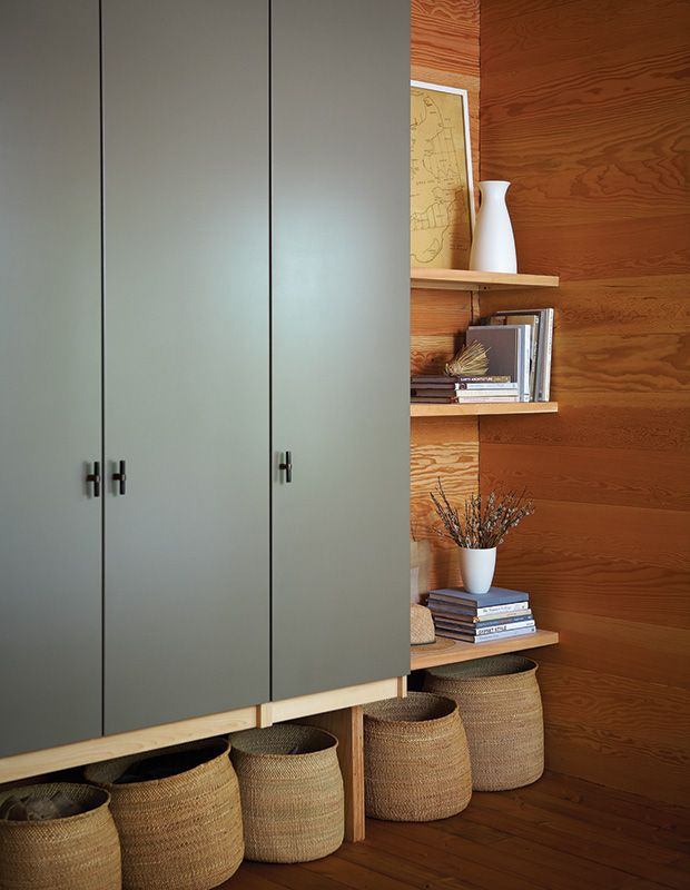 An Ikea Pax wardrobe was custom-painted, fitted with horn handles from Ochre and mounted on the wall to create a floating effect. Extra storage in a row of modern baskets fills the space below.
