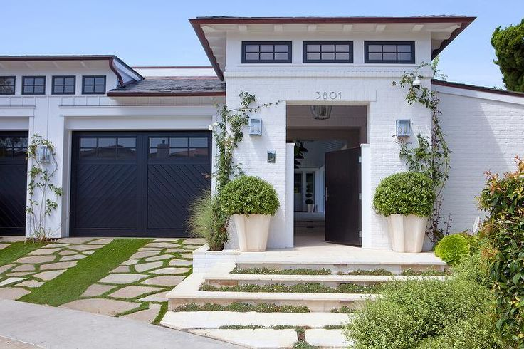White brick home is accented with a black front door with an attached garage with black chevron doors.