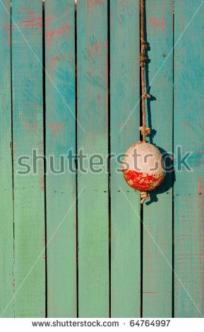 One small white and red fishing buoy hangs on hook in front of brightly painted wooden shack by Jo Crebbin