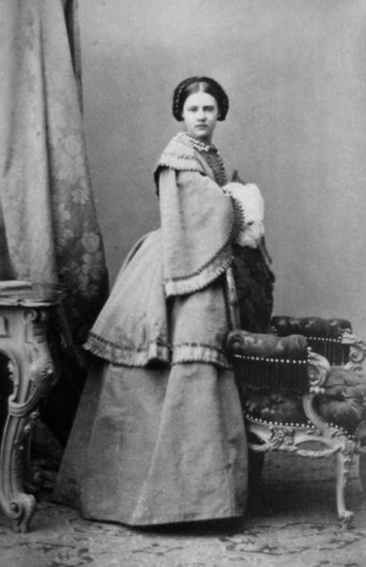 Archduchess Marie Therese of Austria wears a paletot over a narrow skirt, possibly with a bustle. The paletot has a built-in capelet