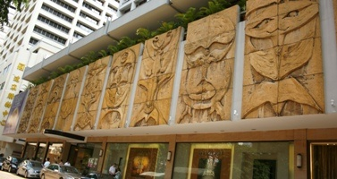 Sculptural Reliefs created by acclaimed Anglo-Chinese muralist and painter Gerard D'Alton Henderson, the stone reliefs span 4,000 square feet and sport Indo-Malay features such as tumpal (isosceles triangle motifs), wayang topeng masks from Indonesian theatrical performance, Singa and other mythical animal faces. The Hilton's owner commissioned the murals when the hotel opened.  Located at: Hilton Singapore