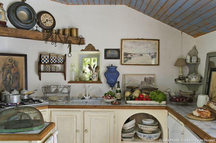 Dans la cuisine, aux côtés des ustensiles viennent s'immiscer des bocaux émaillés, une encoignure festonnée peinte en gris, de la vaisselle en faïence XVIII esiècle et même des aquarelles