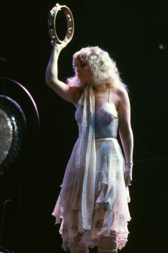Goddess Stevie onstage    ~ ☆♥❤♥☆ ~   with pale, pale hair and a glittery pale pastel stage outfit, tambo raised high  ~ an iconic pose and outfit during Fleetwood Mac's 'Mirage' 1982 tour