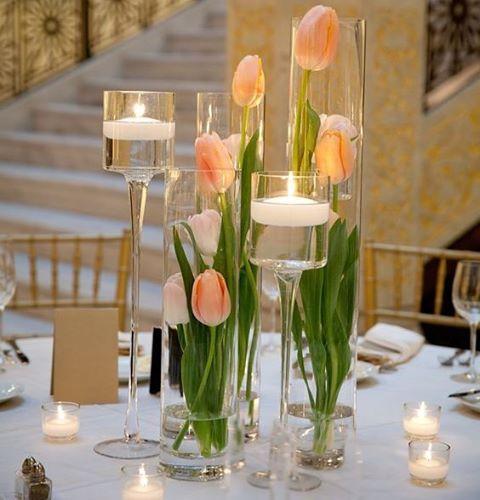 Inspiração clean e bem atual para usar como centro de mesas: tulipas e velas flutuantes, dentro de vasos cilíndricos de vidro. 🌷✨ Este estilo de decoração - velas e flores dentro de vasos - é uma tendência muito usada nas decorações de casamentos contemporâneas, deixando o ambiente com um clima bem aconchegante e romântico. A iluminação do local, onde acontecerá o evento, deve ser bem planejada,...