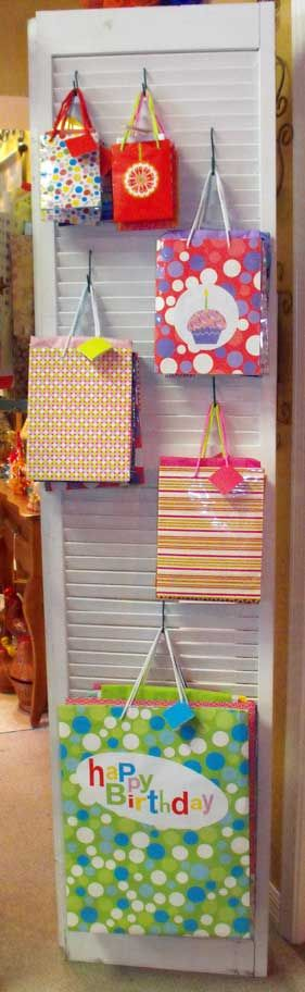 Was going to use a shutter for our bag display but found bi-fold doors instead. It's double-sided and works great for displaying gift bags. #display #store display #retail