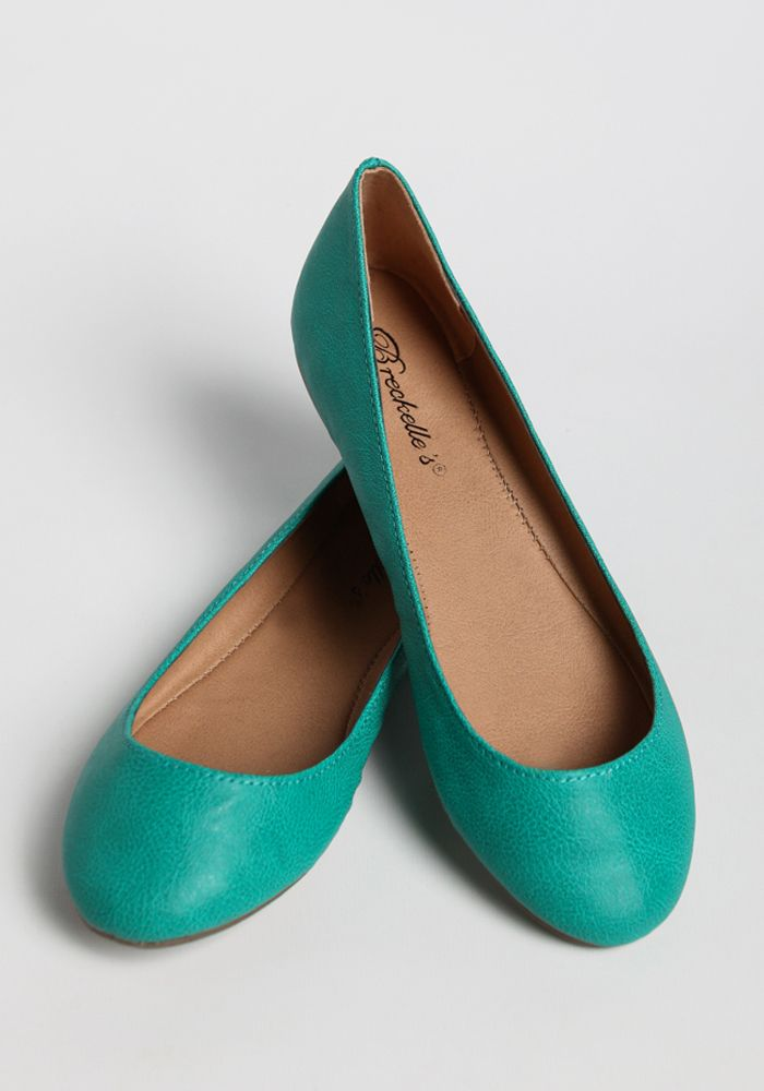 Perfect for adding a pop of color to your ensemble, these stunning teal-colored, faux leather flats feature rounded toes.