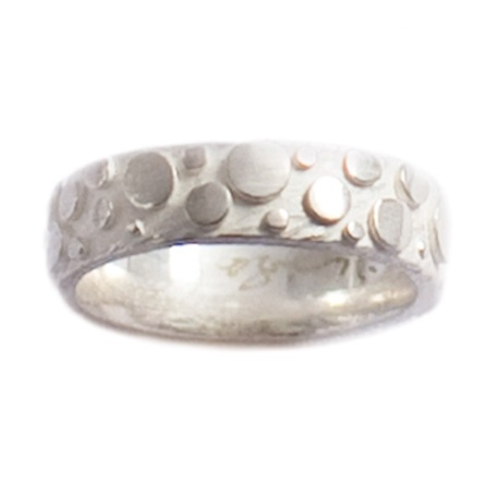 Dahlia Kanner handcrafts the Silver Effervescent Wedding Ring in Rhode Island. This playful ring has a lush background of textured satin-finish sterling silver, a compelling contrast to the high polish silver circles. Spaced at random around the band, the shiny circles seem to bubble up from a boundless source, imbuing this mischievous ring with an extraordinary sense of movement. This band can be matched with the 4mm Oxidized Silver Effervescent Wedding Ring. $250