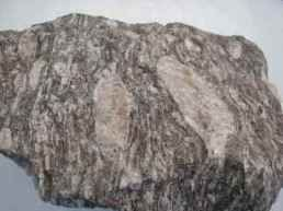Metamórficas: esse tipo de rocha tem sua origem na transformação de outras rochas, em virtude da pressão e da temperatura. São exemplos de rochas metamórficas: gnaisse (formada a partir do granito), ardósia (originada da argila) e mármore (formação calcária). As mais antigas rochas são as do tipo ígneas e metamórficas, que surgiram respectivamente na era Pré-Cambriana e Paleozoica. Essas rochas são denominadas de cristalinas, por causa da cristalização dos minerais que as