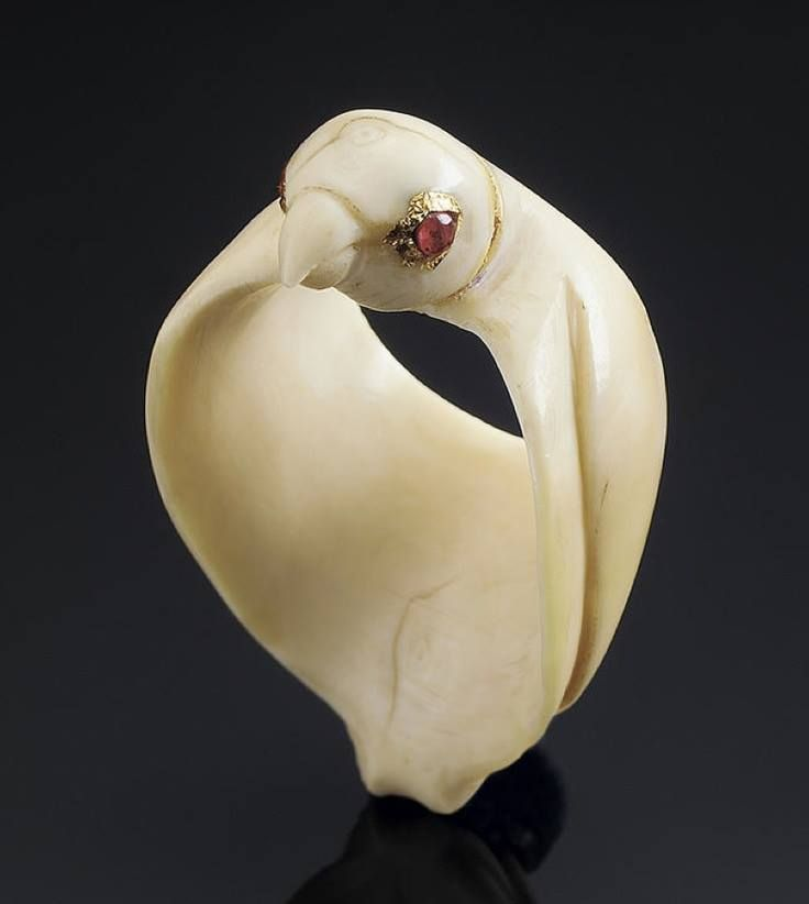 An unusual ivory Archer's Ring in the form of a Falcon probably Mughal, 18th Century formed by a three dimensional bird with ruby-set eyes and folded wings.