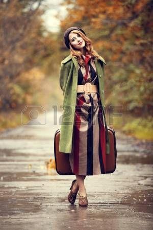 Стиль рыжая девушка с чемоданом на живописной аллее осенью. photo