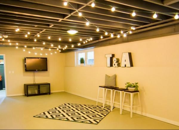 Quick fixes for an unfinished basement: paint walls with stain (not paint so concrete can breathe) and run industrial string lights that only require one outlet.